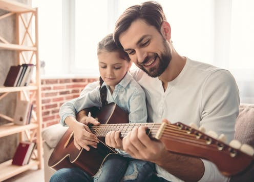 A father and his daughter hold a guitar together in a living room. There is a wooden shelf in front of a low brick wall.
