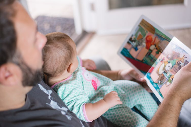 A dad reads to his baby in a blue onesie.