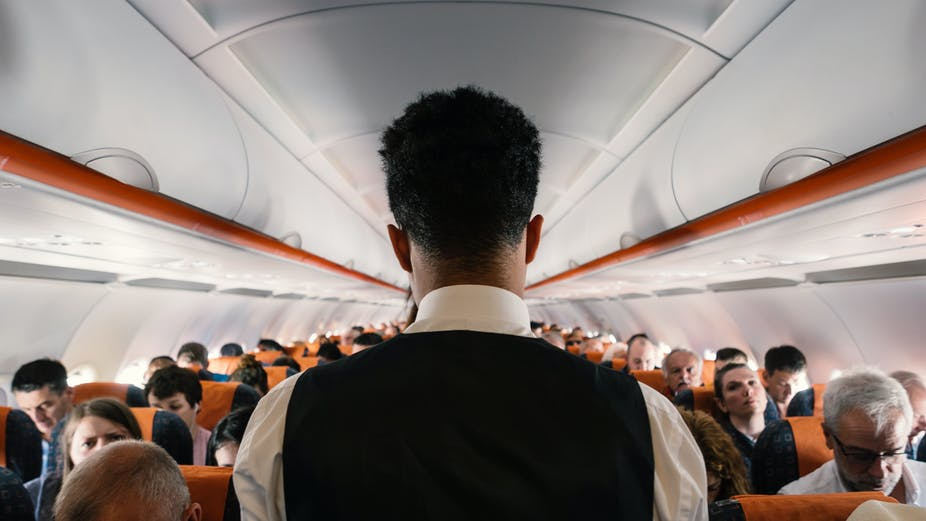 Steward working inside Easy Jet airplane at Gatwick Airport.