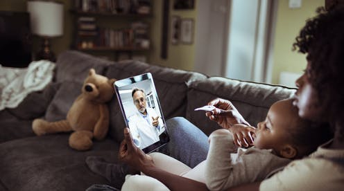 Woman with baby talking to doctor through a video chat.