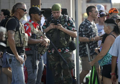 Members of the boogaloo movement. Three men feature prominently in the picture wearing fatigues and Hawaiian shirts.