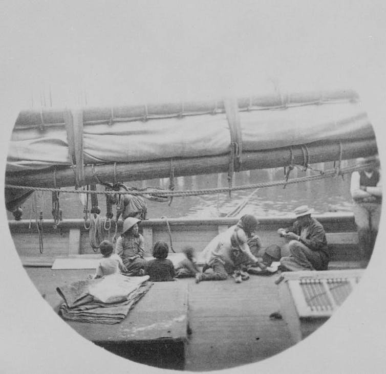 A black and white photo showing a group of Chinese people sitting on the deck of a ship.