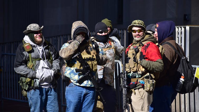 Five men belonging to the boogaloo movement wearing camouflage clothing and carrying guns.