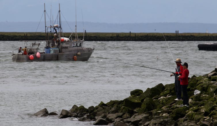 Two men fish off some rocks in B.C. as a commercial fishing boat passes by.