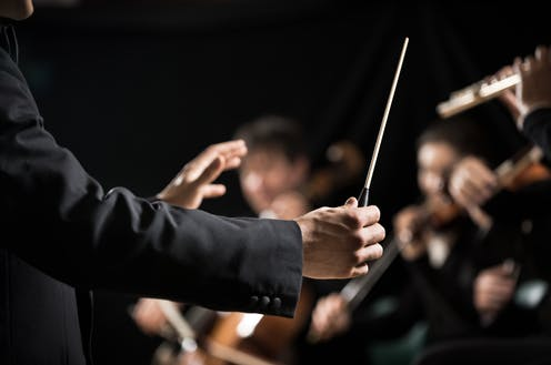 A music conductor guides an orchestra with a baton