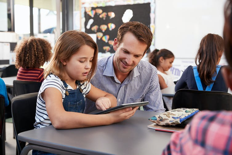 Teacher and girl looking at computer tablet.