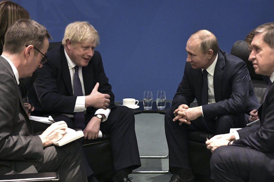 Vladimir Putin and Boris Johnson talking.