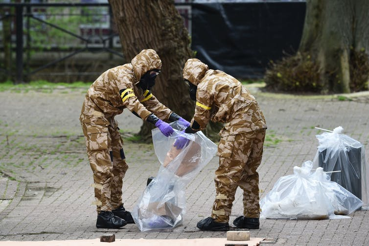 Men in army uniform putting contaminated material in plastic bag