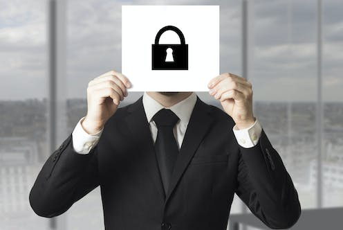 A man in a black business suit holds up a white card with a black symbol of a padlock, obscuring his face.