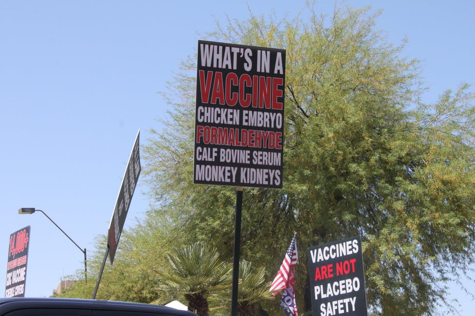 Trump supporters rallying to 'reopen' the economy from COVID-19 safety restrictions carry signs with anti-vaccination myths.