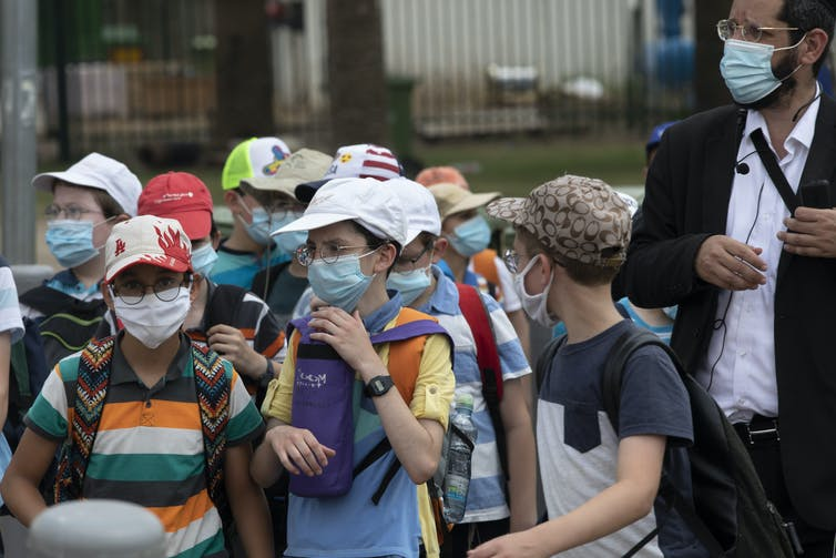 Children wearing face masks walk close together with an adult
