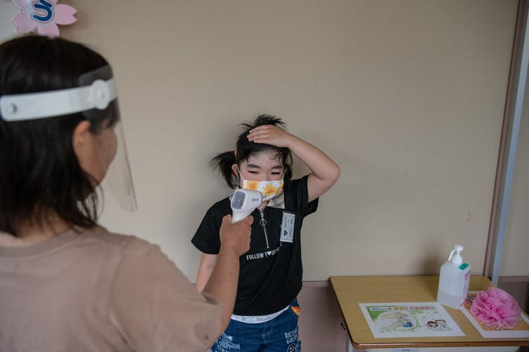Nurse in protective gear takes the temperature of a small child