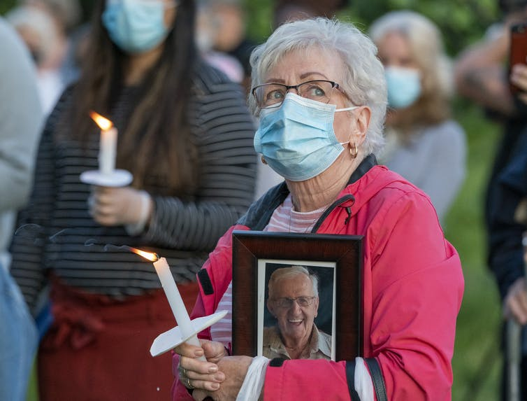 A grey-haired woman wears a mask and carries a candle and a framed photo of an elderly man at a vigil.