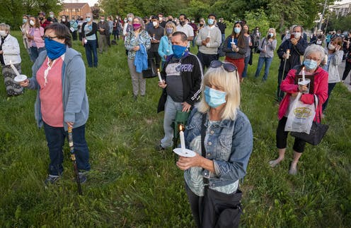 Dozens of people wearing masks, holding candles and some carrying photos stand on the grass outside a long-term care home where many seniors died of COVID-19 in Toronto.
