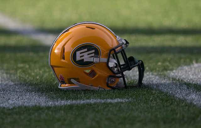 An Edmonton Eskimos football helmet lies on the playing field.