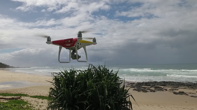 A red and white drone hovers by an empty beach.