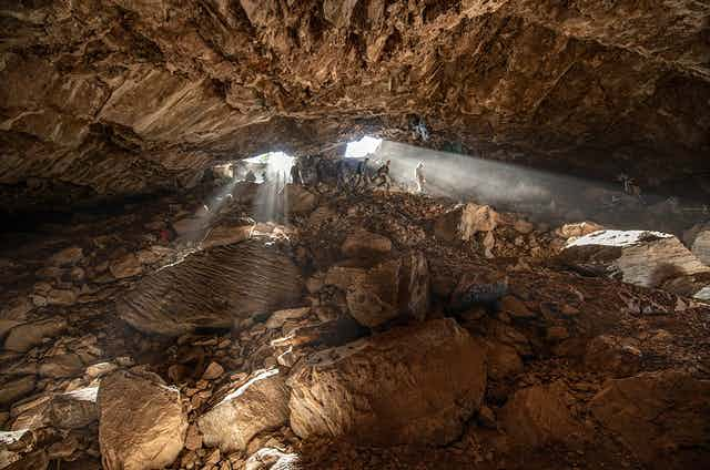 Three people descending into a cave.
