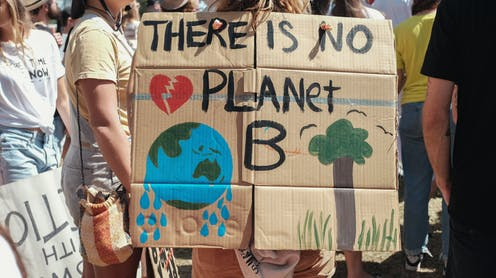 'There is no planet B' is written on a cardboard sign at a protest.