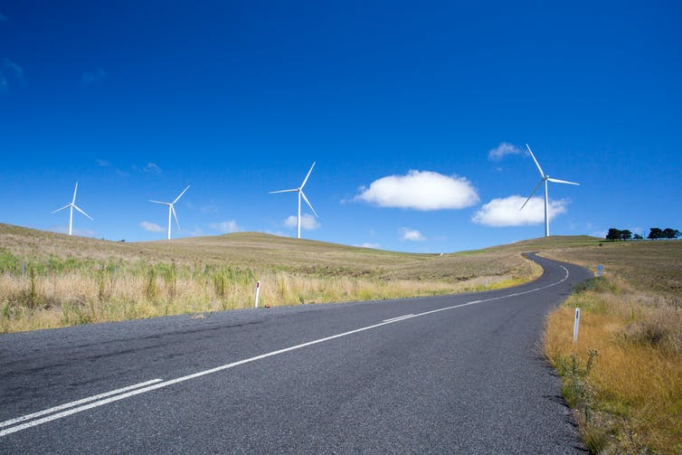 Four wind turbines at the end of a road, flanked by pale green-brown grass.