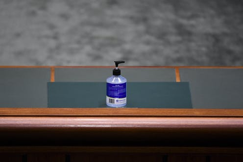 A bottle of hand sanitiser on a House of Representatives table