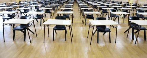 A large exam hall with desks and empty chairs