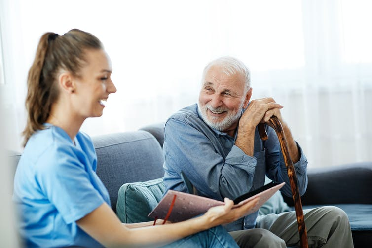 Elderly man sits on the couch happily talking with young female carer.