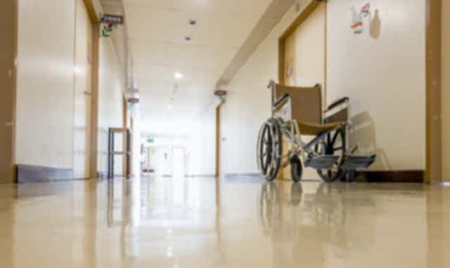 An empty wheelchair sits in the hallway of an aged care facility.