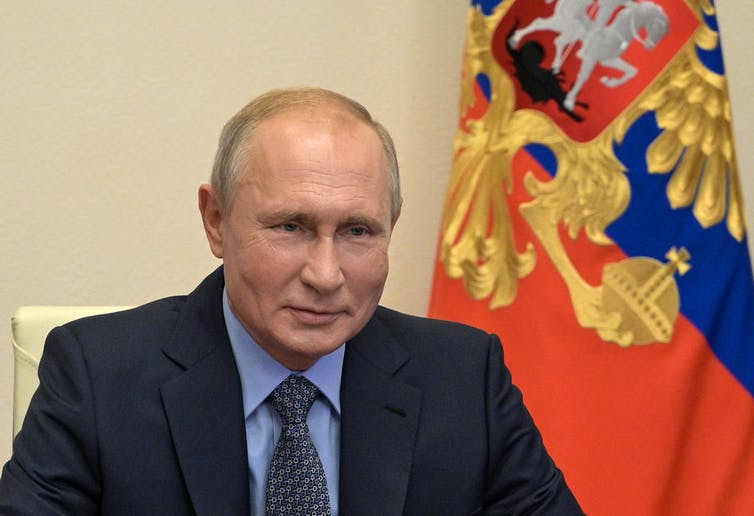 Vladimir Putin with flag behind him
