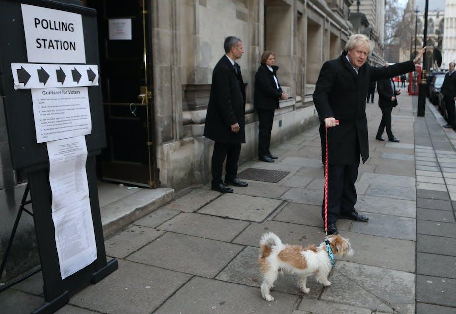 Boris Johnson waving with dog next to sign saying polling station