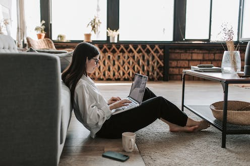 woman working at home sitting on the floor with with her laptop
