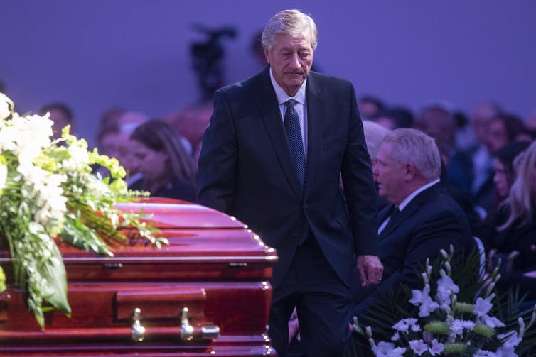 Mike Harris, in suit, tie and overcoat, is seen walking past a casket covered with white flowers.