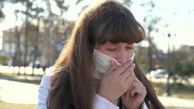 A woman pulling down her face covering to cough into her hand.