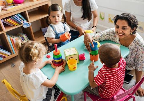 nursery teachers with three children at table