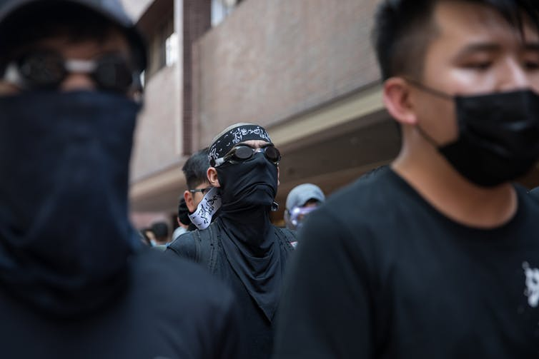Hong Kong protesters dressed in black with face masks