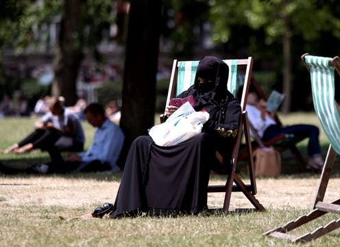 Woman in a burqa sits on a deck chair in a park