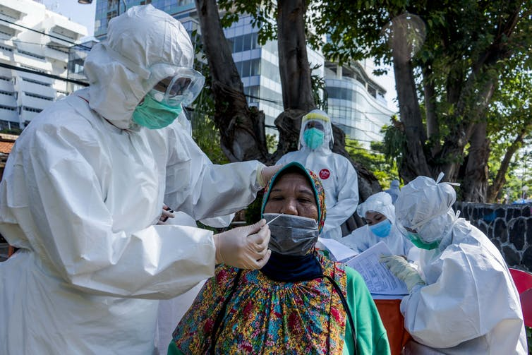 An Indonesian woman is swabbed for a coronavirus test by a man in a hazmat suit.