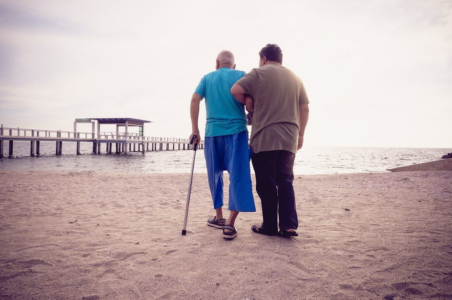 'Son helps his elderly father walk on the beach'