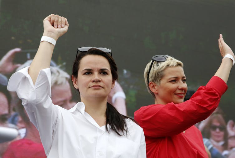 Woman holds up fist next to other woman waving.