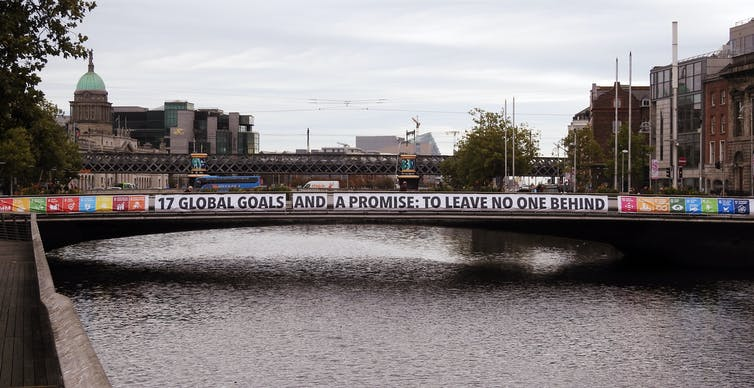 A banner promoting the UN Sustainable Development Goals hangs along the span of a bridge.