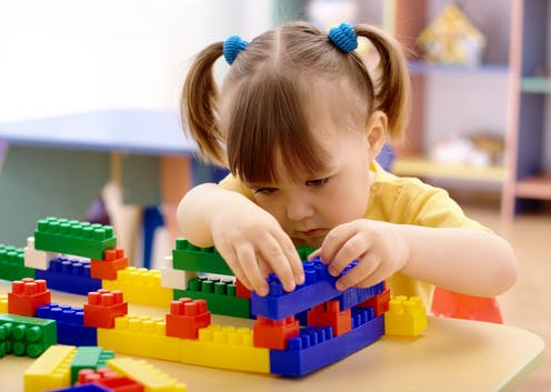 Preschool-age girl playing with plastic building bricks.