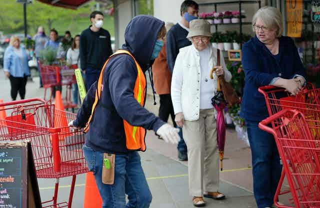 Doorman Dilon Moore, center, helps with shopping carts and controls the number of customers allowed to shop at one time at a Trader Joe's supermarket in Omaha, Neb., on May 7.