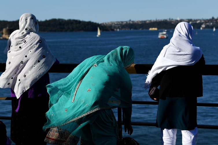 Three Muslim women standing next to a harbour.