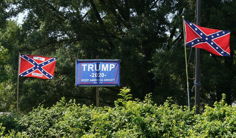 Confederate flags alongside Trump 2020 poster