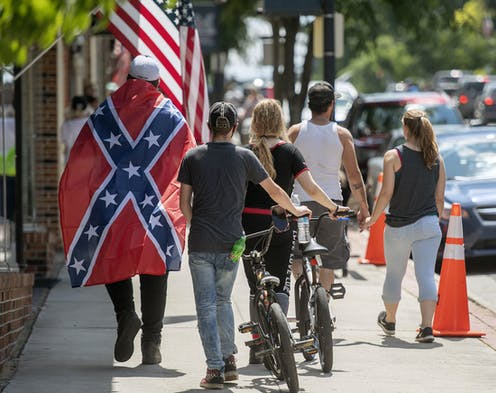 Man draped in Confederate flag walks down street with others
