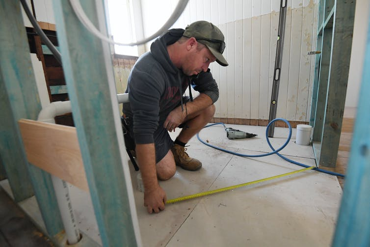A builder measures a room for a home being renovated.
