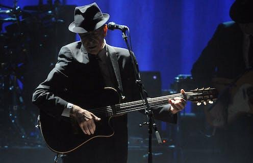 Singer Leonard Cohen in black hat onstage.