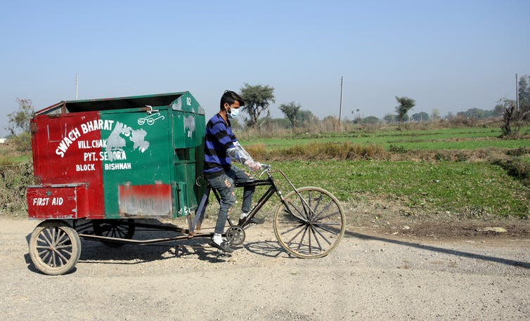 A man in India peddles a bicycle cart to collect rubbish.