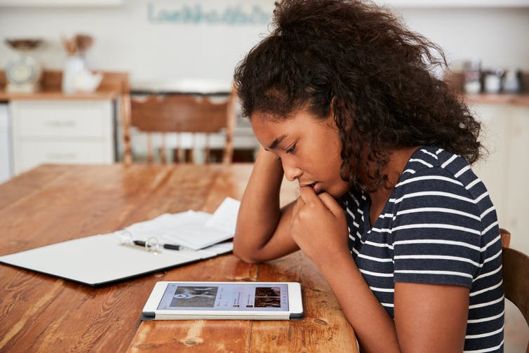Black teenage girl looking at tablet device.