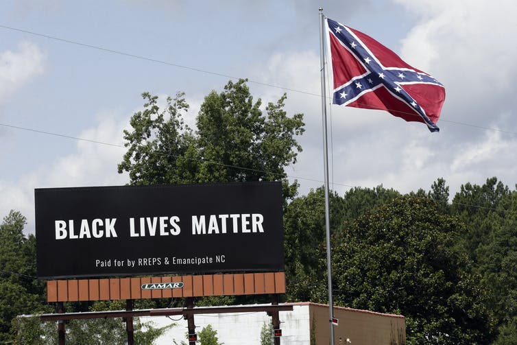 A Black Lives Matter billboard sits next to a Confederate flag, with trees in the background.