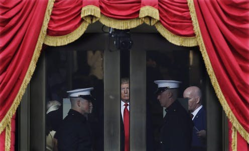 Trump peers through a space between two doors, flanked by military, as he waits to make his inaugural address. Red bunting with gold tassels envelop the scene.